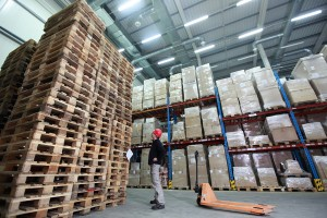 stack of wooden pallets in storehouse - 	worker with hand pallet